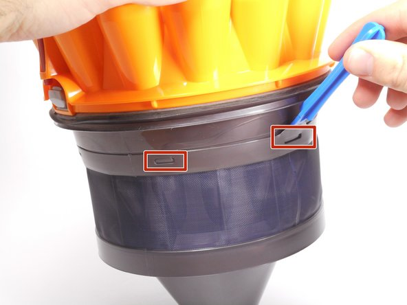 You should notice several notches around the rim of the filter. Slide the plastic opening tool around the rim to release the notches.