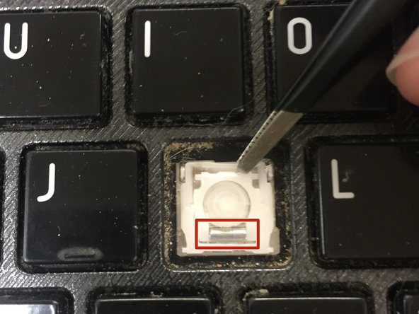 With the edge of the key pad pinched firmly in your pliers, gently pull up with your pliers until the top left and right corners of the key pad pop out of place.