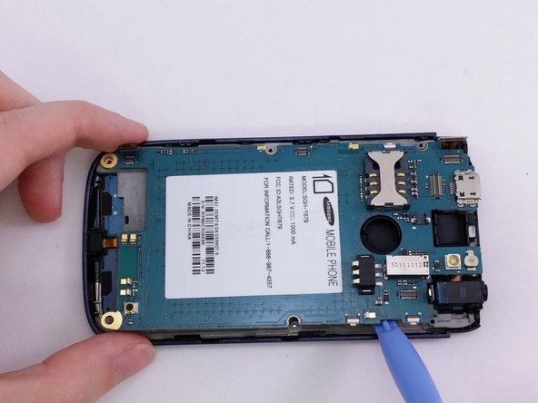 Image 3/3: Insert a plastic pry tool into the gap between motherboard and base of phone