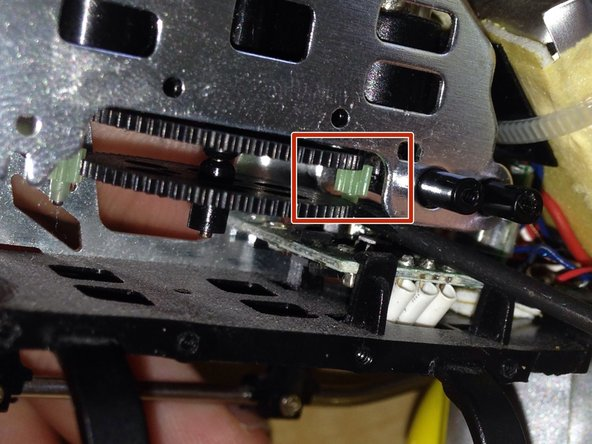 Place the screwdriver's tip underneath the clear motor gear.