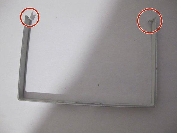 Achtung: An den beiden unteren Ecken ist der Abdeckstreifen mit einer Rastnase ins Gehäuse gesteckt.