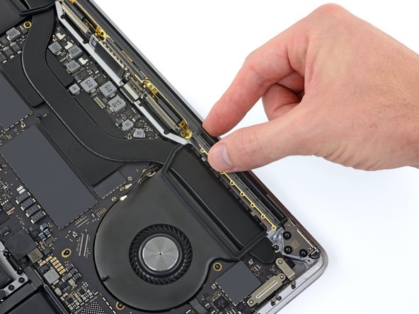 Carefully remove the antenna assembly, while simultaneously feeding the antenna cable bundle out from underneath the heat sink.