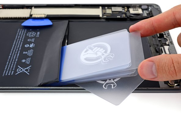 Insert multiple additional cards between the first and second card to create a wedge and lever this section of the battery away from the rear case.