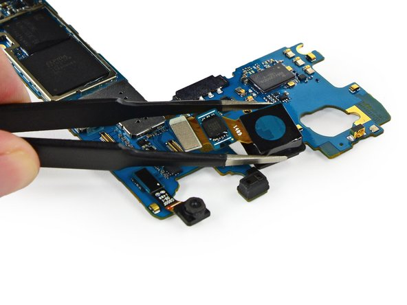 Remove the rear-facing camera from the motherboard using a pair of tweezers.