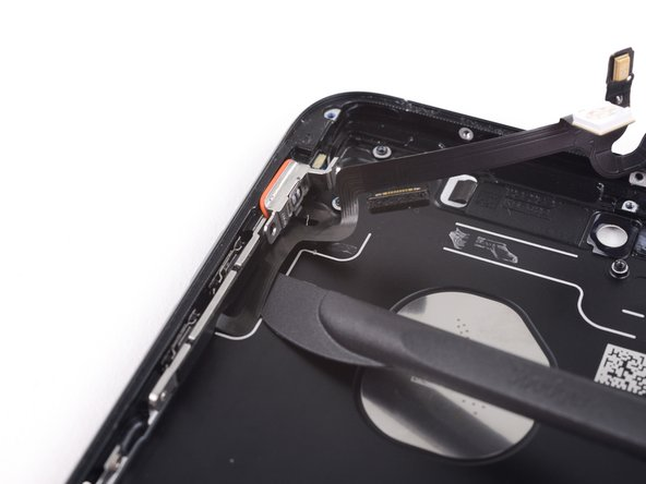 Gently slide the blade underneath the cable towards the bottom of the phone, separating the remaining adhesive.