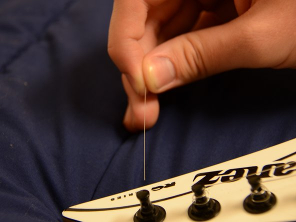 Insert the string into the tuning peg from the right side of the guitar.