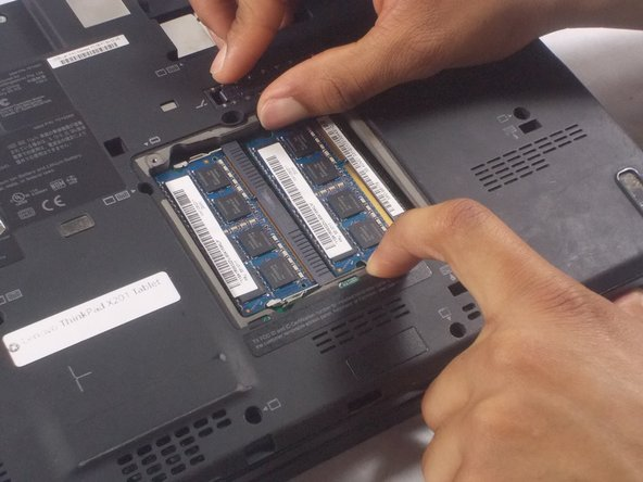 The RAM chip should pop up on its own once the sides are pushed outwards.