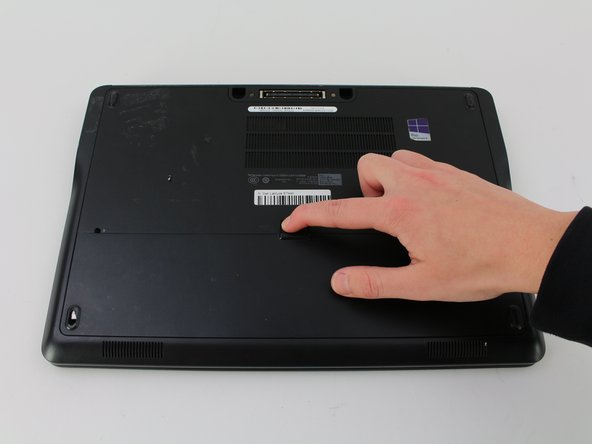 Place your finger on the latch located in the center of the laptop.