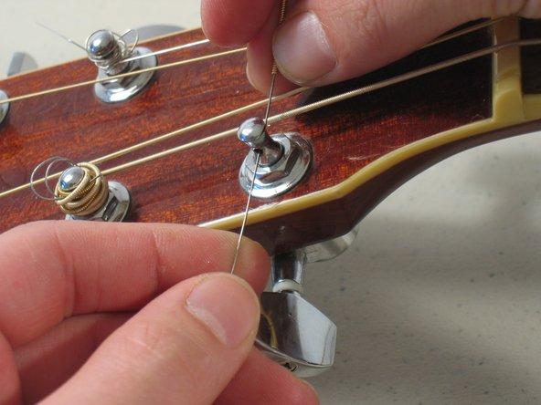 Faites passer l'autre extrémité de la corde de la guitare à travers le trou dans la cheville de guitare.