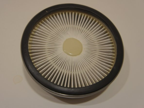 Place new HEPA filter into holder.
