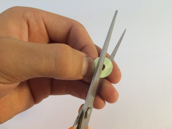 Using scissors, cut out about a third of a new paper shim.