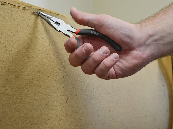 Using a pair of pliers, remove the existing staples from the bottom of the dresser.