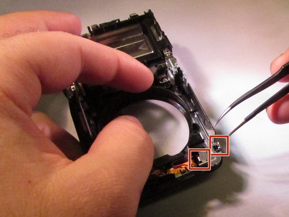 Use tweezers to remove the speaker retaining clip. The retaining hooks locations are indicated, but not exact.