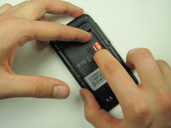 Image 2/2: While keeping pressure on the clip, use another finger to gently slide the SIM card down over the clip.