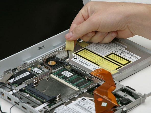 Image 1/1: Peel back the yellow tape securing the inverter cable to the optical drive.