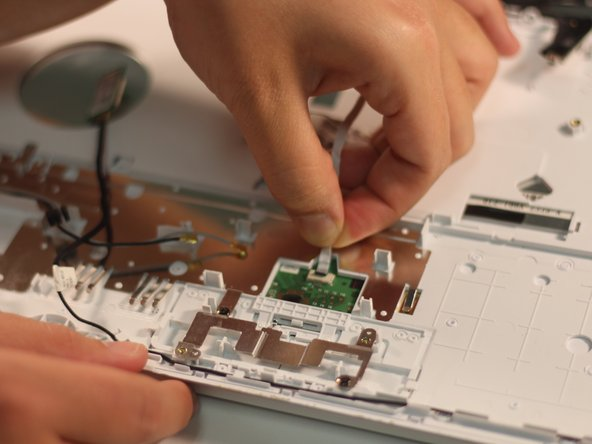 Use your fingers to grasp the ribbon cable. Lightly pull on the cable until it releases.