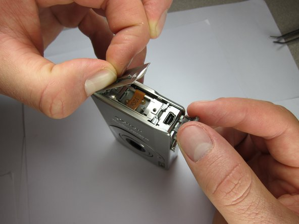 Image 2/2: Gently pull the tab of the side cover and completely detach it from the camera.