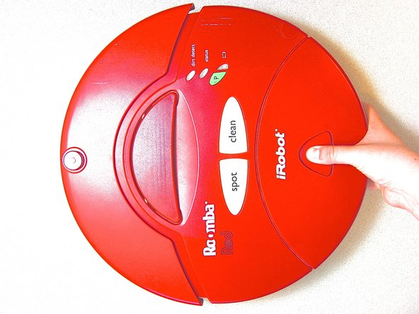 Push in the red, gumdrop-shaped button with your thumb.