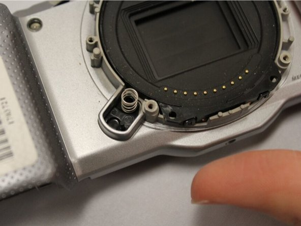 The lens release button and the small spring underneath will be loose.