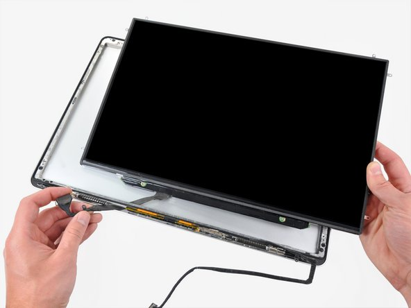Image 1/1: It may be helpful to use one hand to feed the display data cable through its channel in the aluminum display assembly as you pull the LCD toward the top edge of the display with the other hand.