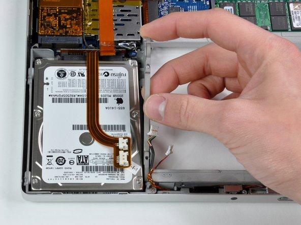 Retira el soporte del disco duro de la carcasa inferior.