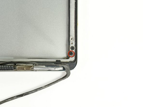 Image 1/1: Remove the 2.2 mm Phillips screw located near the bottom right corner securing the AirPort/iSight cable to the display assembly