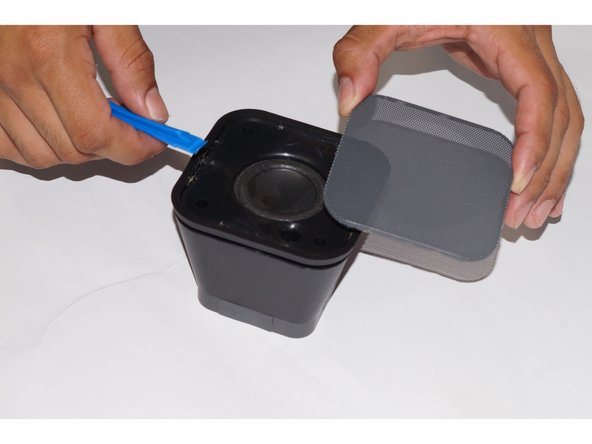 Use the plastic opening tool to pull the metal cover off the top of the speaker.