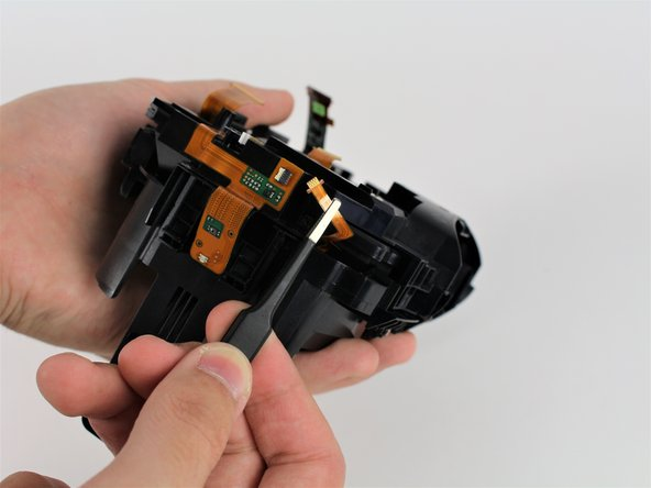 Remove the ribbon cable for the power button by grabbing the cable with tweezers and sliding it outwards horizontally.
