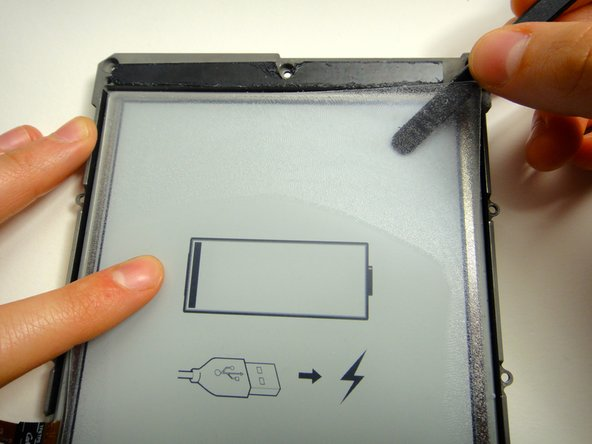 Image 1/2: The plastic screen is held on by a thick layer of glue. Be patient when lifting the screen to avoid bending or breaking the thin plastic.
