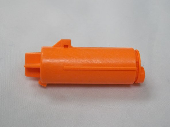 Locate the air plunger in the upper left hand corner of the opened nerf gun. Push back on the spring and carefully pull the plunger toward you to remove it.