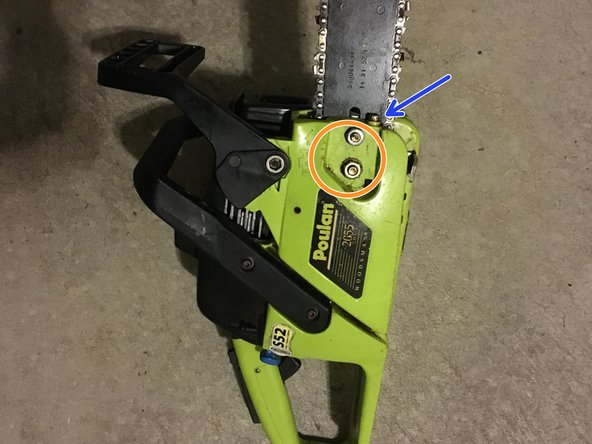 """Loosen the 1/4"""" nuts holding the bar cover in place using the chainsaw T-wrench."""