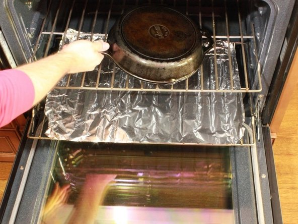 Place the oil coated pan or skillet face down onto the top rack of the oven.