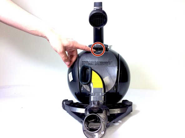 Locate the spring in the small opening between the handle and ball of the vacuum body.