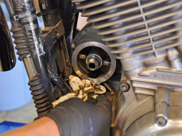 Wipe down the oil filter mounting area, and any oil residue that has run down onto the motorcycle.
