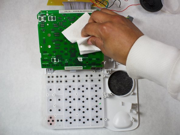 Grab the edge of the number pad board and peel it away from the screw posts.