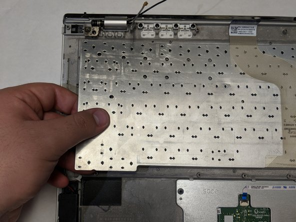 The keyboard will be exposed at this point, simply lift the keyboard from the edges to remove it from the bottom panel of the laptop.