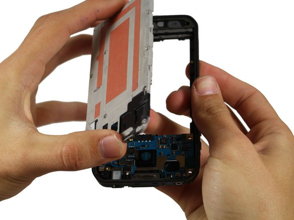 Push upward from the back side your phone (where the battery should go) to pop out the large gray piece.