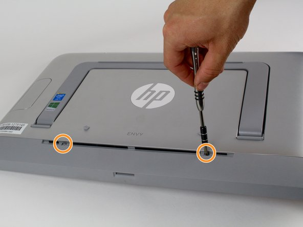 Image 2/2: The screws cannot be removed, they just unscrew from the interior components of the computer.
