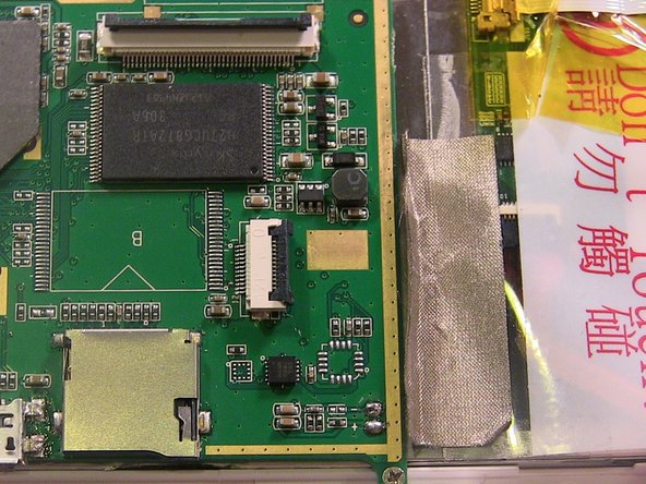 On the bottom of the motherboard, a strip of gold tape will be seen holding the it to the device.