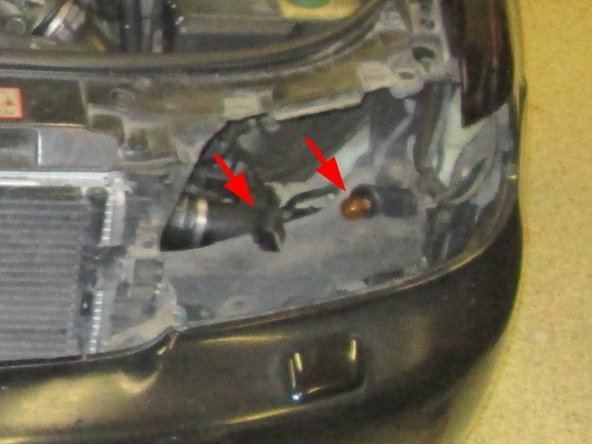 Connect the cabling back up to the rest of the car (arrow on left), reattach the blinker light to the assembly (arrow on right), and push the assembly back into place.