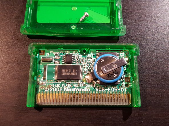 Flip the cartridge over and carefully push the front half of the casing down, you can now take the front off and remove the game from the plastic casing.