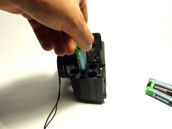 Remove four AA batteries one by one from the camera, making note of the proper alignment.