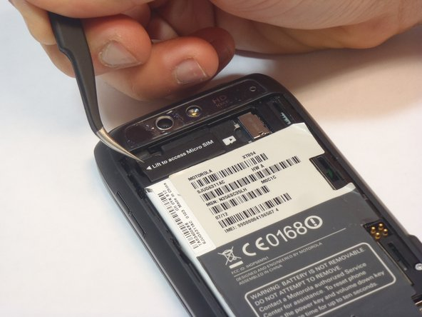 Using tweezers or your finger, lift the rubber SIM card cover to expose the card itself.
