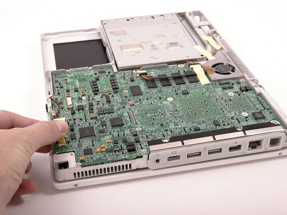 Image 1/1: Turn the computer over and disconnect the orange hard drive cable, removing tape as necessary.