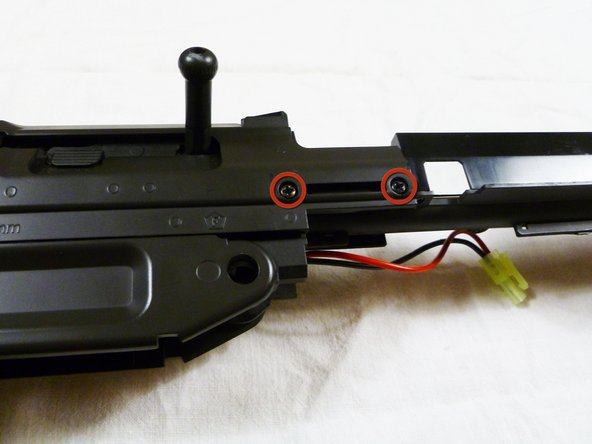 Using a Phillips #1 screwdriver, remove the two 8mm screws above the hand guard on both sides of the gun.