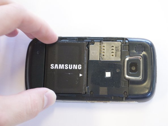 Grip the battery on its sides, opposite the direction of the white arrow.