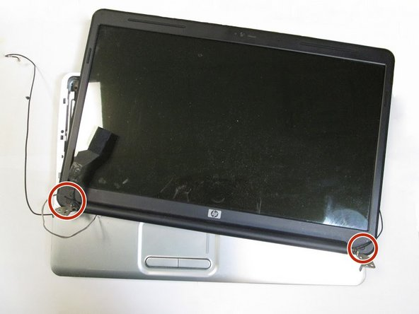 Use the spudger to remove the rubber sticker located at the bottom of each side of the screen.