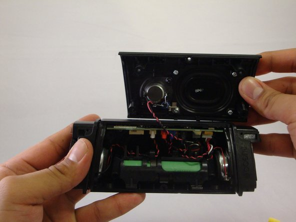 Image 3/3: Using the plastic opening tool, you will be able to wedge back face of speaker off.
