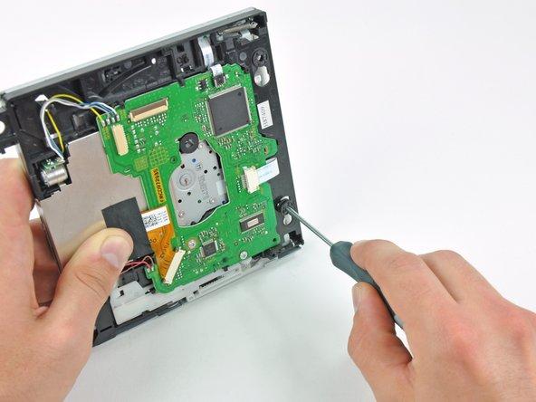 細長いドライバーの先端を内蔵DVDドライバーの正面に沿って下部に装着されたゴム製「はと目金」中央の穴に差し込みます。