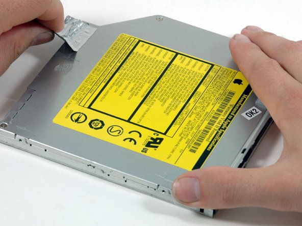 Image 1/1: Peel up the silver foil tape from the optical drive.